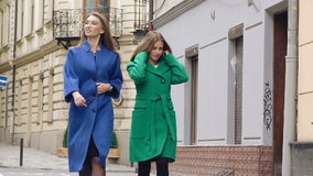 Two assured women walks runway in cashmere wool coats on the street. Slowly.  stock video