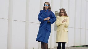 Two assured women walks runway in cashmere wool coats on the street. Slowly.  stock video footage