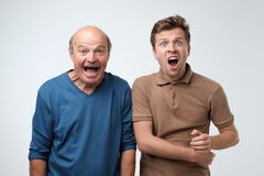Two astonished men keeping mouths opened, shouting in shock stock images