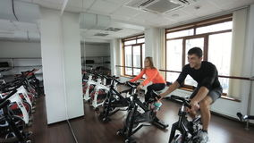 Two Athlete engaged on a stationary bike in gym. This simulator develops main muscles of legs, calf and thigh biceps, quadriceps.Wall in front of them a mirror stock video footage