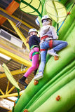 Two athlete girls climbing on artifical green tree Stock Photography