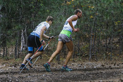 Two athlete runners running uphill in woods Royalty Free Stock Photos