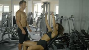 Two athlete trainer girl and boyfriend, a man stands, and a girl shakes his arm muscles with a dumbbell under the. Supervision of a coach, a healthy lifestyle stock video footage