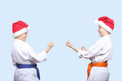 Two athletes in caps of Santa Claus standing in rack of karate Royalty Free Stock Photography