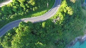 Two athletes come down the mountain on the asphalt road next to the sea. Morning cardio. HD aerial shot. stock video footage