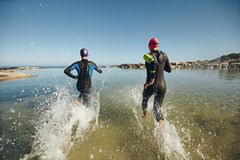 Two athletes competing in a triathlon Royalty Free Stock Images