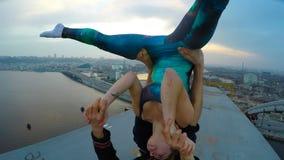 Two athletes doing acro yoga exercises on bridge, risky hobby, extreme sports. Stock footage stock video footage
