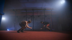 Two athletes doing difficult crossfit exercise at the same time. Two athletes doing difficult crossfit exercise at the same time in gym. Athletes greet each stock footage