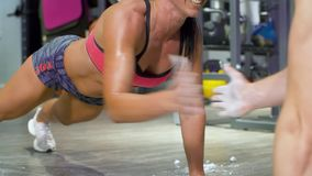 Two athletes doing push ups face to face and clapping hands. Athletic training in gym. Fitness, sport, exercising, training concept stock footage