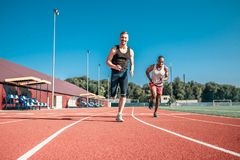 Two athletes finish cheerfully. Two athletes fun finish in the stadium Royalty Free Stock Photography