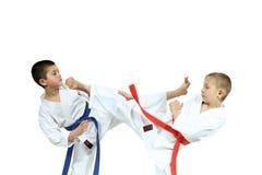Two athletes in karategi are beating blows Yoko geri Stock Photo