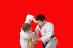 Two athletes in kimono are training techniques capture hands and blow. Two athletes are training techniques capture hands and blow Stock Photos