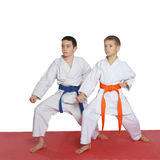 Two athletes with orange belt and blue belt stand in rack Stock Image