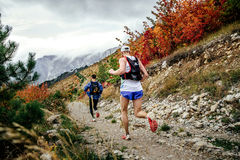 Two athletes runners running from mountain along trail in autumn landscape. Yalta, Russia - October 5, 2016: two athletes runners running from mountain along stock images