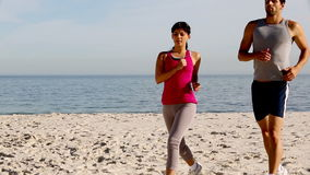 Two athletes running on the beach. Two athletes running and taking a break on the beach stock footage