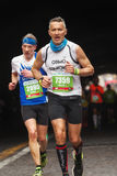 Two athletes running the marathon, full length, vertical. Rome, Italy - April 2nd, 2017: Two athletes of the 23rd Rome Marathon taken to the passage of the Royalty Free Stock Photography