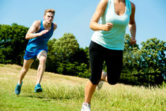 Two athletes running through meadows. Image of two athletes racing countryside Stock Photos