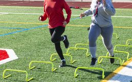 Two athletes running over yellow banana hurdles stock photo