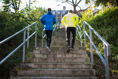 Two athletes running on stairs in sunny autumn, rear view. Royalty Free Stock Images