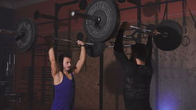 Two athletes at the same time lift the bar with weight. In gym. Camera moves. Joint crossfit training of best friends stock video