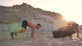 Two athletes train in active mode on the beach doing push-UPS and pushing a huge wheel