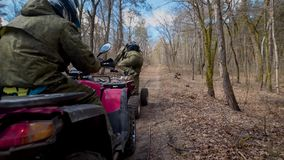 Two athletes who wear protective helmets and clothes jump on the ATV and swiftly ride along the autumn forest. Wo athletes who wear protective helmets and stock video footage