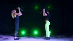 Two athletic, beautiful, women doing strength exercises with heavy weight plates, at night, in light smoke, fog, in. Light of multicolored searchlights, in an stock video