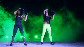 Two athletic, beautiful, women doing strength exercises with heavy weight plates, at night, in light smoke, fog, in stock footage