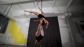 Two athletic beautiful young women twirl around on a pole