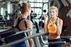 Two athletic blond women talking in gym. Girl communicates with trainer. Two athletic blond women talking in the gym. Girl communicates with the trainer Royalty Free Stock Images