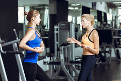 Two athletic blond women talking in gym. Girl communicates with trainer. Two athletic blond women talking in the gym. Girl communicates with the trainer Royalty Free Stock Photography