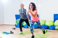 Two athletic female friends working out in a gym doing reverse lunge knee-up exercise stock photography