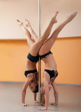 Two athletic girl stand on hands during pole dance Stock Images