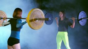 Two athletic girls, athletes, raise the barbell, do sit-ups with the barbell. At night, in the light of searchlights, in stock footage