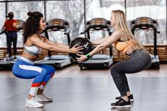 Two athletic girls dressed in a sportswear are doing together back squats with heavy fitness ball in the modern gym royalty free stock photos
