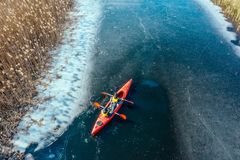 Two athletic man floats on a red boat in river stock photos