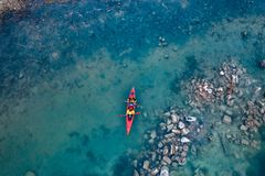Two athletic man floats on a red boat in river royalty free stock photos