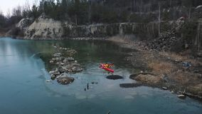 Two athletic man floats on a red boat in river. Two athletic man floats on a red boat in calm blue waters river stock video