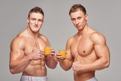Two athletic men with glasses of orange juice Royalty Free Stock Image