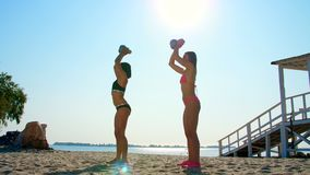Two athletic, sexy young women in swimsuit, coaches, instructors, perform, doing exercises with weights. On the beach stock video footage