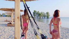 Two athletic, sexy young women in swimsuits, instructors, doing exercises with fitness trx system, TRX suspension straps stock footage