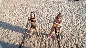Two athletic, sexy young women in swimsuits, instructors, doing exercises with fitness trx system, TRX suspension straps stock video