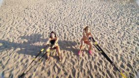 Two athletic, sexy young women in swimsuits, instructors, doing exercises with fitness trx system, TRX suspension straps stock video footage