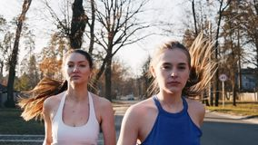 Two athletic woman running outdoors in slow motion on concrete track in park. Healthy fitness concept.  stock footage