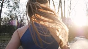 Two athletic woman running outdoors in slow motion on concrete track in park. Healthy fitness concept.  stock video footage