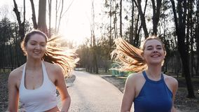 Two athletic woman running outdoors in slow motion on concrete track in park. Healthy fitness concept.  stock video
