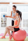 Two athletic woman training with fitball and dumbbells Stock Photography