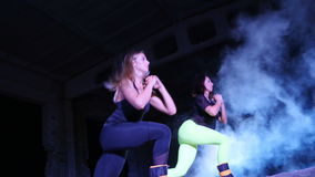 Two athletic women, doing various fitness exercises with weighting on their legs, At night, in light smoke, fog, in. Light of multicolored searchlights, in an stock video