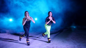 Two athletic women, doing various fitness exercises with weighting on their legs, at night, in light smoke, fog, in. Light of multicolored searchlights, in an stock video footage