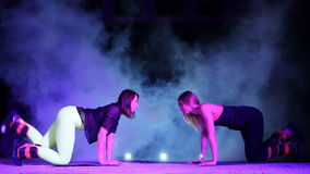 Two athletic women, doing various fitness exercises with weighting on their legs, At night, in light smoke, fog, in. Light of multicolored searchlights, in an stock footage